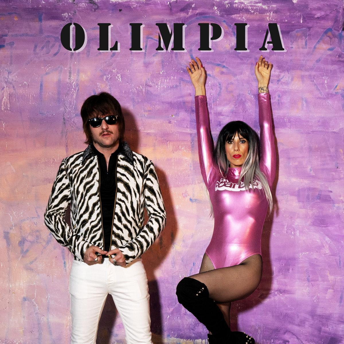 Hombre con gafas de sol cerrándose la chaqueta de zebra y mujer con body rosa con brazos levantados sobre fondo violeta
