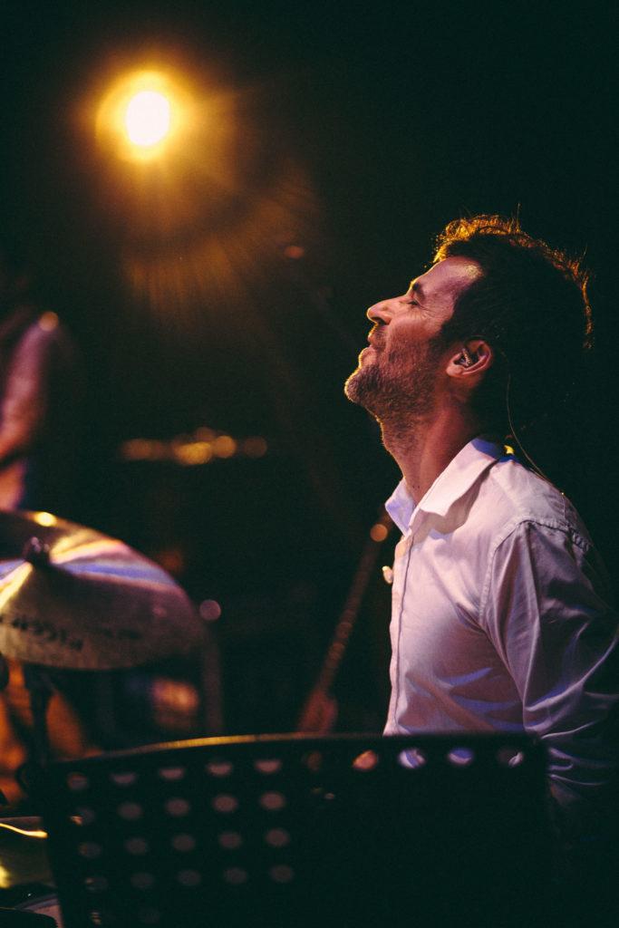 El batería Oriol Flores sonriendo mientras toca, su cabeza mira al cielo y un foco le ilumina