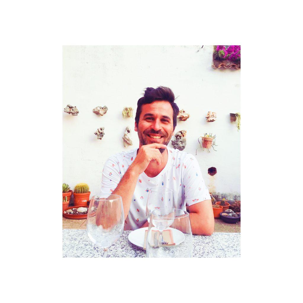 Oriol hombre joven sonríe en espacio con plantas y flores mediterráneas