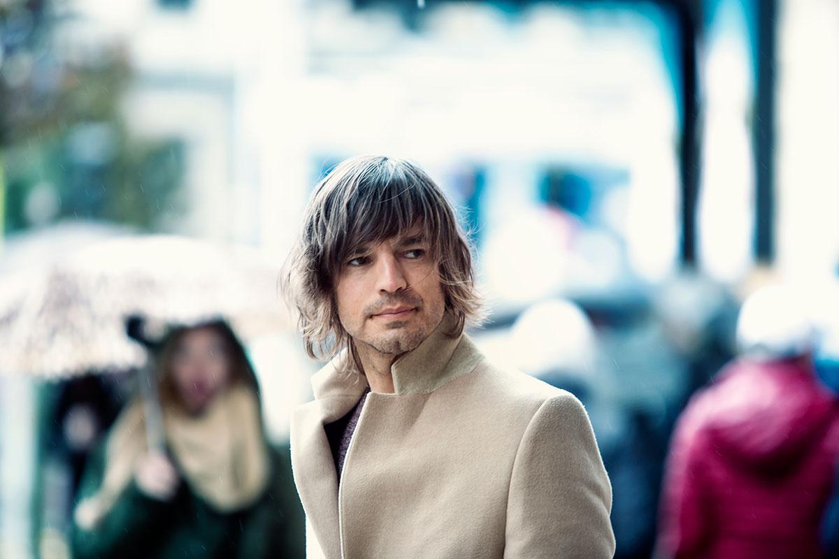 Hombe con abrigo beige en centro de ciudad